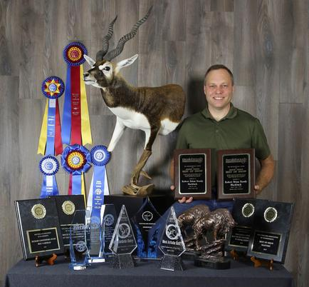 Brain standing with his mount and awards